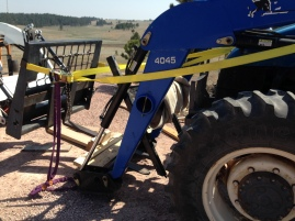 Strapping the loader to Cowboy's tractor to prevent it from tilting and falling