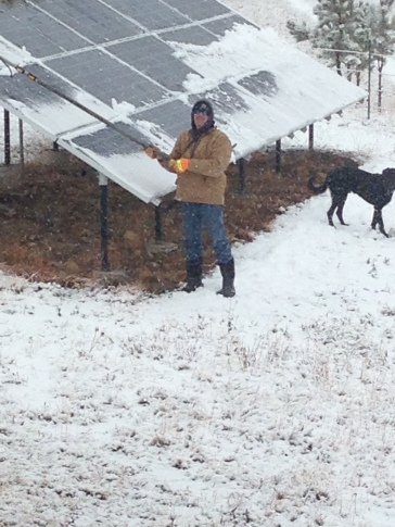 Rancher Dave scraping snow off the solar panels