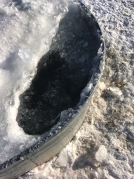 A hole in the ice for about 3 heads to get water